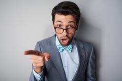 有玻璃指向的滑稽的惊奇的年轻人 免版税库存照片
