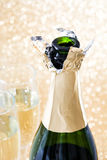 有玻璃杯子的香宾开放瓶在精采金黄背景 免版税库存图片