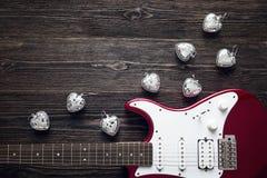有玻璃状心脏的红色电吉他在一黑暗的木backgrou 免版税库存图片