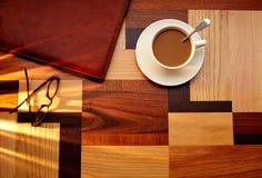 有玻璃的咖啡杯在桌减速火箭的葡萄酒 免版税库存照片