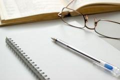 有玻璃的在桌上的笔记本和笔 免版税库存图片