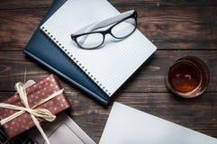 有玻璃的笔记本,礼物,膝上型计算机,在木书桌上的杂志 库存图片
