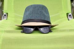 有黑玻璃的草帽在一把绿色椅子 免版税库存图片