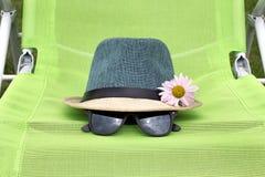 有黑玻璃的草帽在一把绿色椅子 免版税库存照片