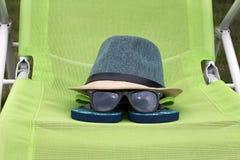 有黑玻璃的草帽在一把绿色椅子 库存照片
