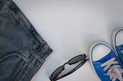 有玻璃的蓝色青年运动鞋在白色木背景 免版税库存照片