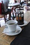 有玻璃茶壶的茶杯在咖啡馆桌上 免版税库存照片