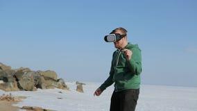 有玻璃虚拟现实的一个年轻人 海岸在春天 影视素材
