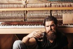 有玻璃近的木钢琴的有胡子的人 免版税库存照片