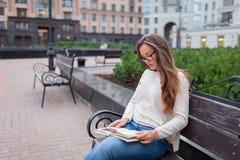 有玻璃长的棕色头发的年轻美丽的女孩坐与书的一条长凳 她在一个温暖的晚上离开房子写入 库存图片
