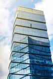 有玻璃门面的摩天大楼反对蓝天背景 免版税库存照片