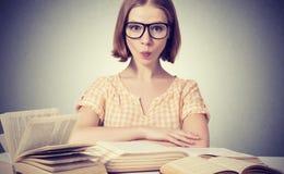 有玻璃阅读书的滑稽的女学生 免版税库存照片