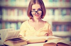 有玻璃阅读书的滑稽的女学生 免版税图库摄影