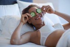 有黄瓜切片的少妇在床上 免版税库存照片
