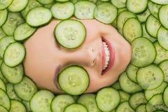 有黄瓜切片面部面具的美丽的妇女在面孔的 图库摄影