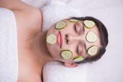 有黄瓜面具的美丽的妇女在她的面孔 免版税库存图片