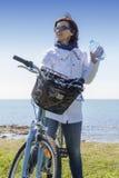 有水瓶的中间年迈的健康妇女在登山车 免版税库存图片