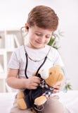 有医生审查的玩具熊听诊器的可爱的孩子  库存图片