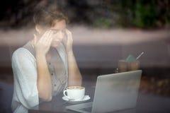 有头疼妇女年轻人 射击通过窗口 免版税图库摄影