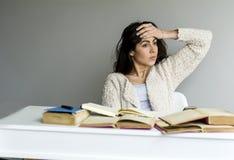 有头疼学习的疲乏的少妇 库存图片