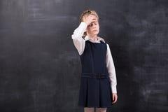 有头疼的女小学生站立在黑板 库存照片