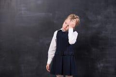 有头疼的女小学生站立在黑板 免版税库存照片