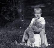 有黑白的玩具熊的哀伤的小男孩 库存图片