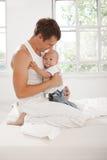 有他的九个月的年轻父亲在床上的儿子在家 免版税图库摄影