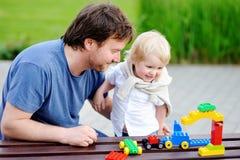 有他的使用与五颜六色的塑料块的小孩儿子的父亲 免版税库存图片