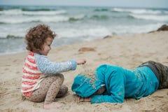 有他的使用在海滩的姐妹的男孩 免版税库存照片