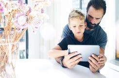 有他的使用片剂个人计算机的年轻儿子的有胡子的父亲在晴朗的屋子里 一起使用在移动计算机上的爸爸和小男孩,休息  库存照片