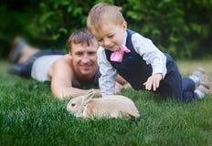 有他的使用用在草的一只兔子的父亲的小男孩 图库摄影