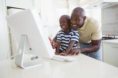 有他的使用计算机的儿子的愉快的微笑的父亲 库存照片