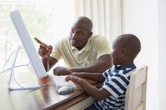 有他的使用计算机的儿子的愉快的微笑的父亲 免版税库存图片