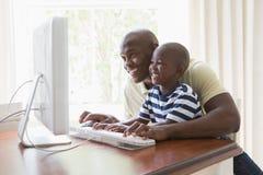 有他的使用计算机的儿子的愉快的微笑的父亲 免版税图库摄影