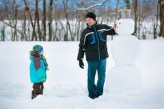 有他的做雪人的父亲的小男孩 免版税库存照片