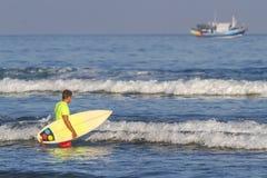 有他的冲浪板的冲浪者。 免版税图库摄影