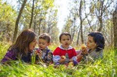 有他们的吃苹果的孩子的两个母亲 库存照片