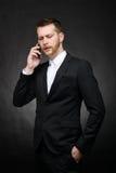 有年轻的商人在智能手机的一次严肃的交谈 免版税库存图片