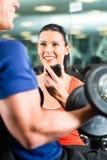 在健身房和哑铃训练的个人教练员 免版税图库摄影
