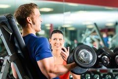 在健身房和哑铃训练的个人教练员 库存照片