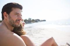 有他的坐在海滩的女朋友的体贴的年轻赤裸上身的人 库存照片