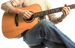 有他的声学吉他的吉他弹奏者 免版税图库摄影