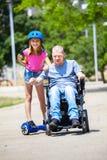 有他的女儿的残疾父亲hoverboard的获得乐趣在Th 免版税库存照片