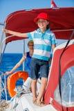 有他的姐妹的男孩上尉在船上在夏天巡航的航行游艇 旅行冒险,乘快艇与家庭的孩子 免版税图库摄影