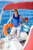 有他的姐妹的男孩上尉在船上在夏天巡航的航行游艇 旅行冒险,乘快艇与家庭的孩子 库存图片