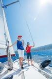 有他的姐妹的男孩在船上在夏天巡航的航行游艇 免版税库存照片
