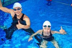 有他的学生游泳的迷人的教练在水池 免版税库存照片