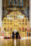 有他们的孩子的两名虔诚妇女走向圣Ekaterina正统大教堂祈祷和崇拜 垂直里面视图 库存图片