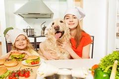 有他们的宠物的女孩在准备膳食的厨师的帽子 库存照片